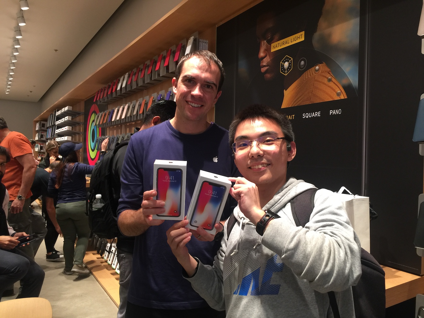 Satisfied customer popoway holding two iPhone X boxes with an Apple employee.